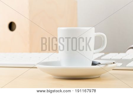 Office desk with cup folders and laptop with empty screen copy space - workplace or coffee break concept