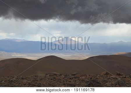 Awe-inspiring landscape of the puna salteña from the snowy of Acay, with a low ceiling of natural clouds
