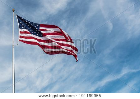 American Flag against the backdrop of a blue partly cloudy sky.
