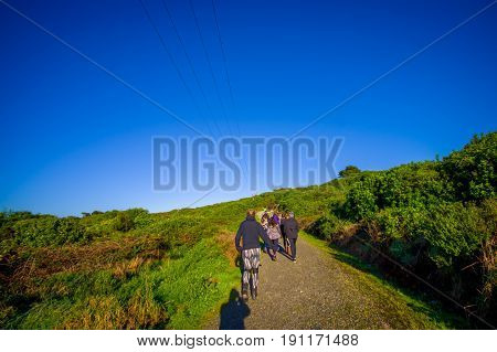 Family hiking a mountain in a beautiful sunny day, South Island, New Zealand.
