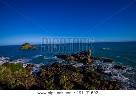 Island near Cape Foulwind, View from the Cape Foulwind walkway at the Seal Colony, Tauranga Bay. New Zealan.