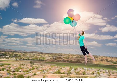 Young Girl Being Carried Up and Away By Balloons That She Is Holding Above The Town Below.
