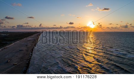 aerial drone view above padre island as the sun rises over the Gulf of Mexico on a nice calm morning on the beach