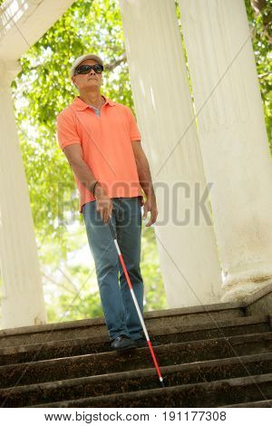 Blind Man Walking And Descending Stairs In City Park