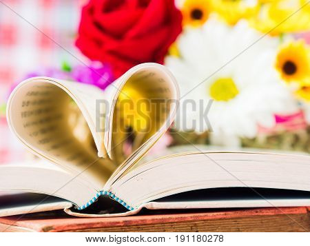 opened book and pages forming heart shape with flower in backgroung. LOVE and valentine's day concept.