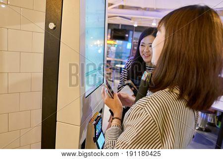 SEOUL, SOUTH KOREA - CIRCA MAY, 2017: women use McDonald's ordering kiosk. McDonald's is an American hamburger and fast food restaurant chain.