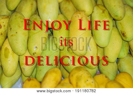 English Quote Enjoy Life Its Delicious with blurry fresh fruit manggo as background.