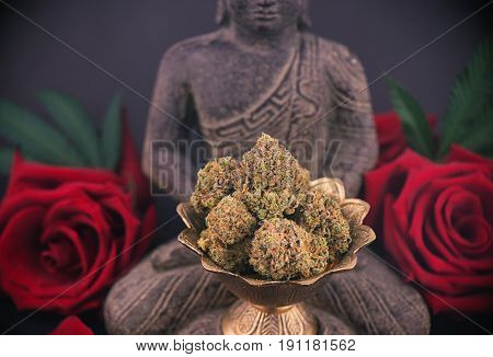 Zen smoky background with buddha statue, red roses and cannabis buds - medical marijuana and meditation concept