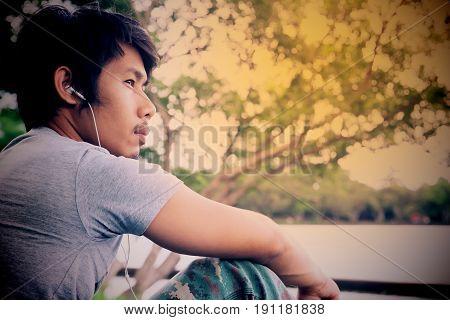 Asian broken heart man listening music Vintage style color Dark tone