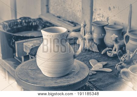 Old vintage photo. Clay jug on a potter's wheel close-up. Copy spase