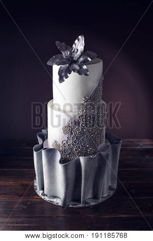 Large Wedding Cake Decorated With Beads And Silver Flower
