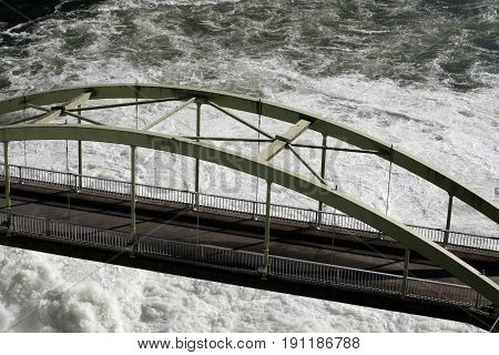 Bridge over rushing white water from a dam on a river.