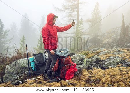 Hiker Travels In The Mountain Forest In The Mist With A Backpack And Trying To Find A Mobile Connect