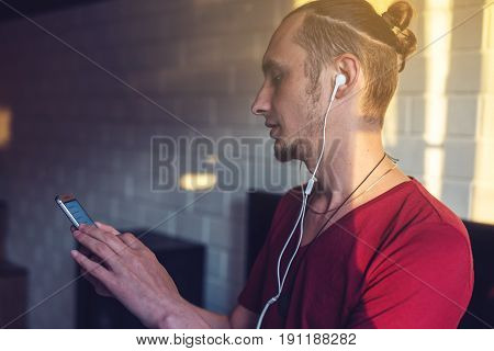Handsome, A Music Lover Listens To Music With Headphones With A Mobile Phone On The Media And Large