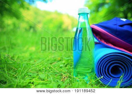 Fitness outdoors background background with copy-space. Water sport carpet and backpack close-up on green grass. Summer sport background.