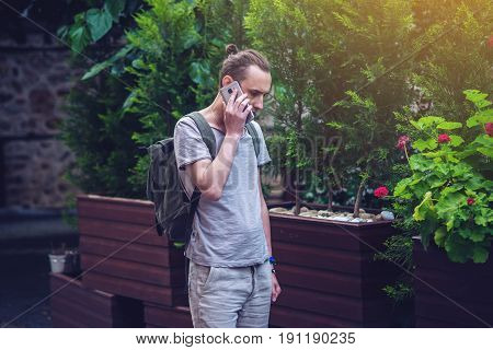 Man Traveler With Backpack Talking On The Phone In Park City