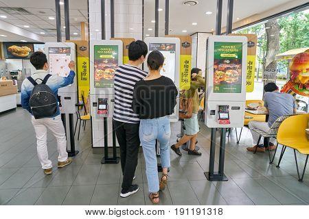 SEOUL, SOUTH KOREA - CIRCA MAY, 2017: people use McDonald's ordering kiosks. McDonald's is an American hamburger and fast food restaurant chain.