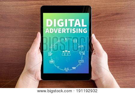 Two Hand Holding Tablet With Digital Advertising And Icon On Screen At Dark Brown Table Top,digital