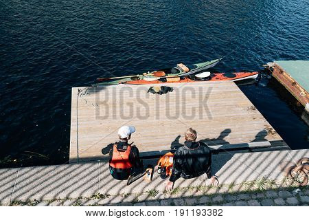 Copenhagen Denmark - August 11 2016: Canoeists resting after exercise sitting on waterfront of Copenhagen in a sunny summer day.