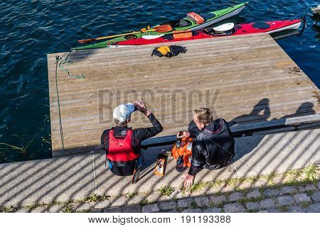 Copenhagen Denmark - August 11 2016: Canoeists resting after exercise and drinking beer sitting on waterfront of Copenhagen in a sunny summer day.