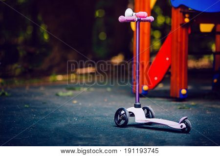 Children's three-wheeled scooter against the backdrop of a children's playground. Concept is a fashionable means of transportation in the summer.