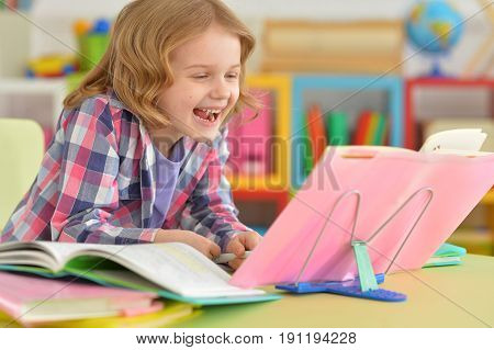 Portrait of a smilimg little girl reading book