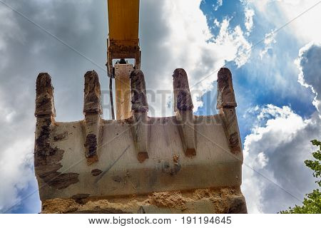 Excavator bucket with large teeth against the sky with clouds and clouds