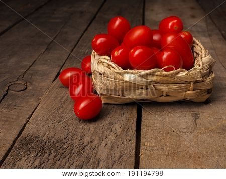 Fresh organic grape tomatoes on a rustic wooden table with space for text