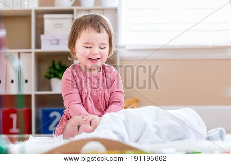 Happy Toddler Girl Playing With Her Baby Sister