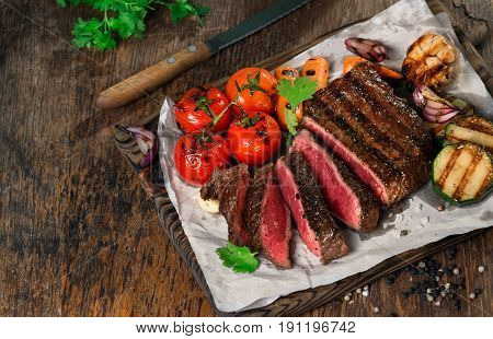 Sliced rare grilled steak on rustic cutting board with set of grilled vegetables on dark rustic wooden table with copy space for your text