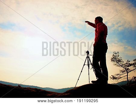 Nature Photographer With Tripod On Cliff And Thinking. Dreamy Fogy Valley Below