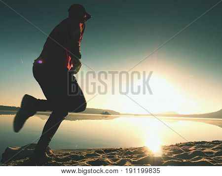 Man Exercising  And Stretching On The Lake Beach At Sunrise. Healthy Lifestyle. Alone Young Fitness