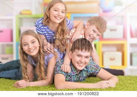 Group of children lying on floor with green carpet and having fun