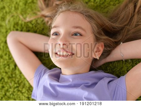 Funny smiling little girl lying on green carpet