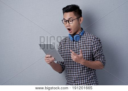 Astonished young man in eyeglasses and checked shirt using digital tablet while standing against gray background, waist-up portrait
