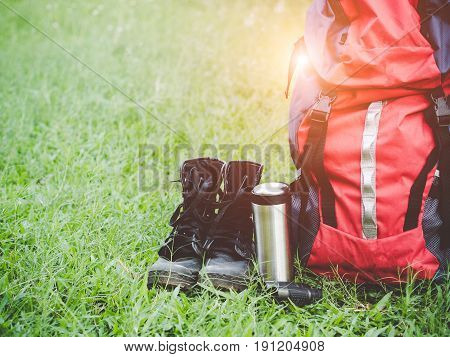 Hiking travel gear on glasses. Items include hiking boots cup mapbinoculars. Flat lay of outdoor travel equipment items for mountain camping trip.
