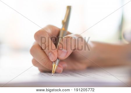 Hand with pen over application form .