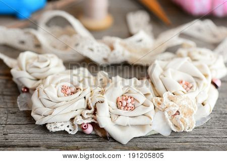 Cute shabby chic necklace on a vintage wooden background. Female flower necklace made of cotton fabric, lace ribbons and beads. Simple way to turn old cloth into jewelry. Closeup