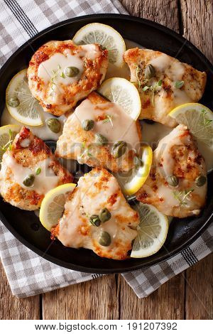 Italian Food: Chicken Piccata With Sauce, Lemon And Capers Close-up. Vertical Top View