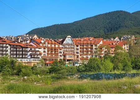 Bansko, Bulgaria - June 13, 2017: St. Ivan Rilski hotel and green pine trees mountains panorama in bulgarian ski resort Bansko