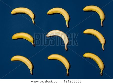 Nine yellow bananas lying in rows on blue background.