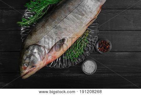 Cutting Fresh large Fish Siberian Chum salmon on glass plate dark black wooden background. Spices for fish dog-salmon pepper salt thyme tarragon knife.