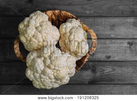 Fresh white heads cleaned cauliflower in a wicker basket for cauliflower. Rustic gray wooden background. Top view blank space.