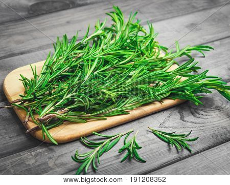 Branches of rosemary on gray wooden table. Rosemary on cutting board. Rustic style fresh organic herbs.