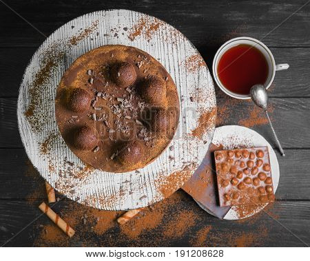Chocolate cake torte covered with cocoa powder and decorated with truffle. Ingredients for Chocolate cake torte Chocolate waffles sticks truffles and Chocolate bars tea. Dark black wooden background. Top view.