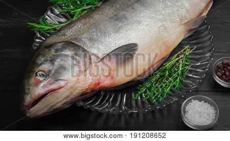 Cutting Fresh large Fish Siberian Chum salmon on glass plate dark black wooden background. Spices for fish dog-salmon pepper salt thyme tarragon knife.