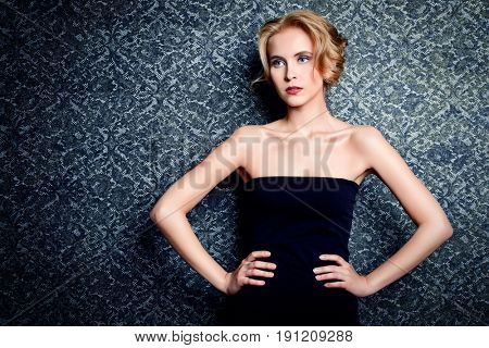 Charming young woman with evening hairstyle and make-up posing in black dress over vintage background. Beauty, fashion.