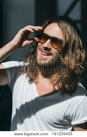 Close-up Portrait Of Handsome Smiling Young Man Adjusting Sunglasses And Looking Away