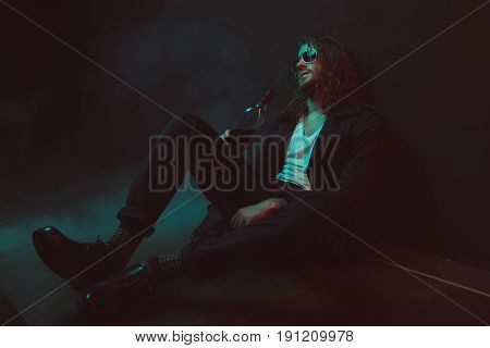 Young Drunkard In Sunglasses Drinking Whiskey From Bottle While Sitting On The Floor