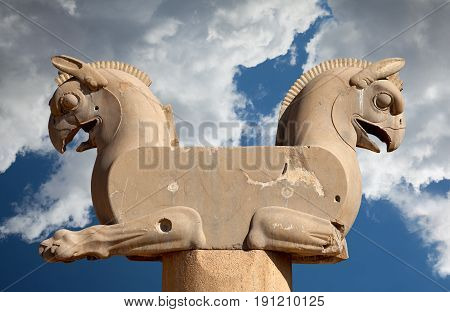 Twin Homa or Huma the Griffin bird figures used as decorative capital statuary of a column in Persepolis of Shiraz against blue sky with white fluffy clouds.